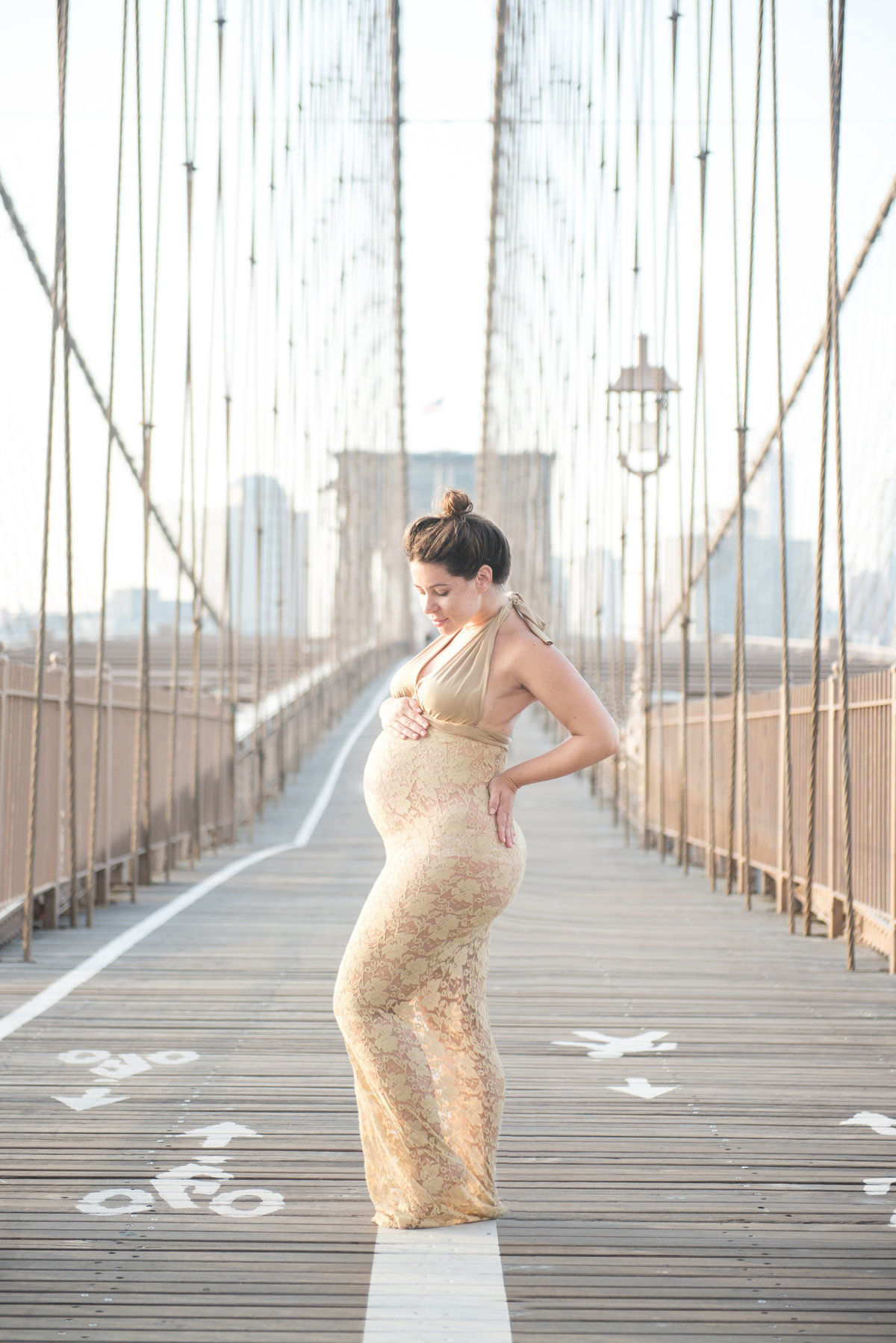 pregnant mom in gold lace dress on the brooklyn bridge