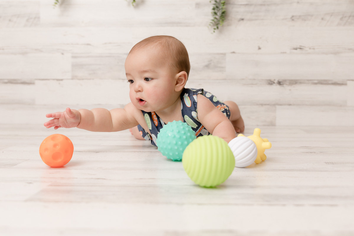 Baby boy reaches for colorful balls