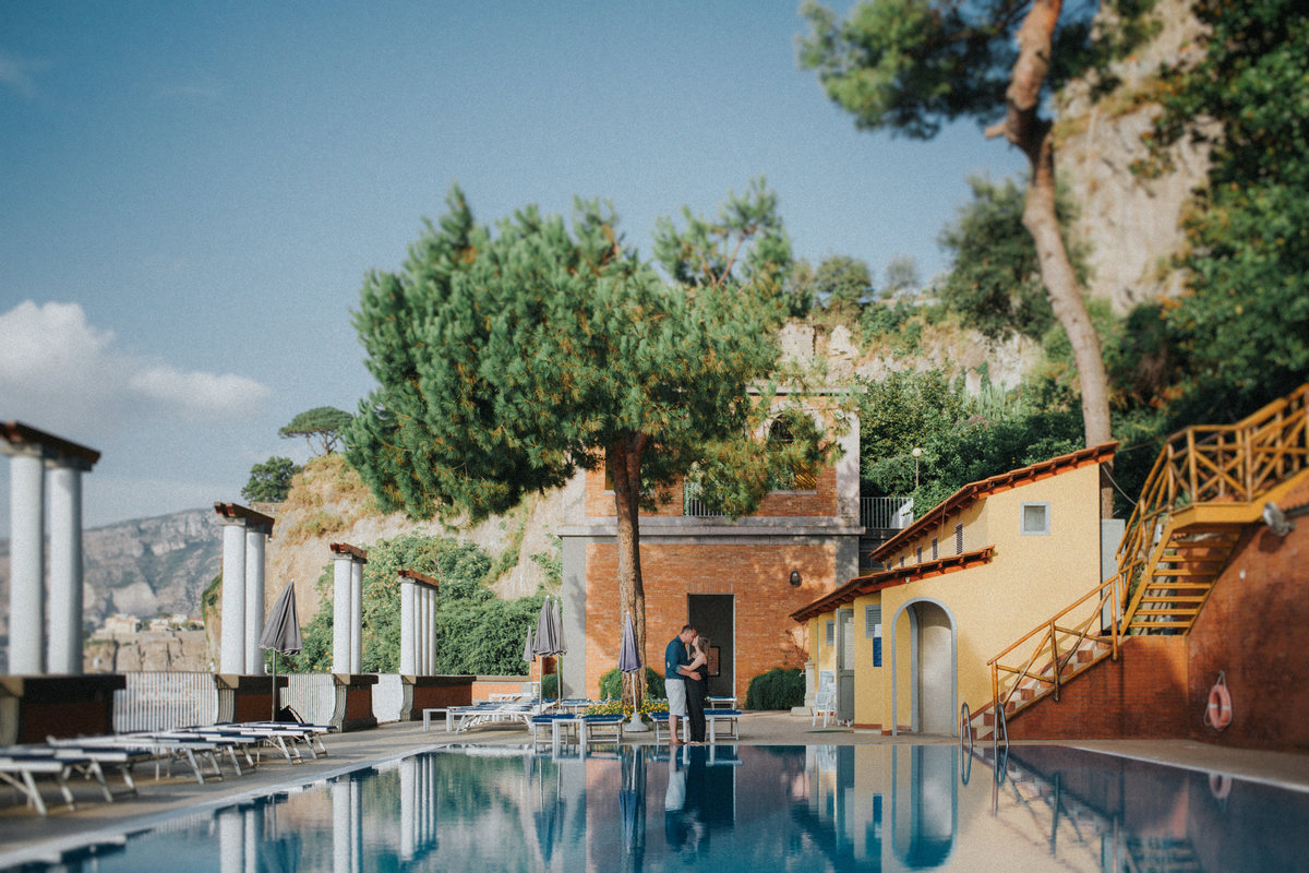 Destination Wedding Photographer Jono Symonds - Photo of couple embracing and kissing in front of a swimming pool in Sorrento, Italy