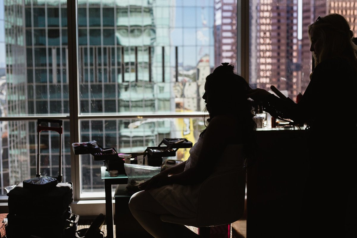 Silhouette of bride getting ready in downtown Phoenix by wedding photographer PMA Photography.
