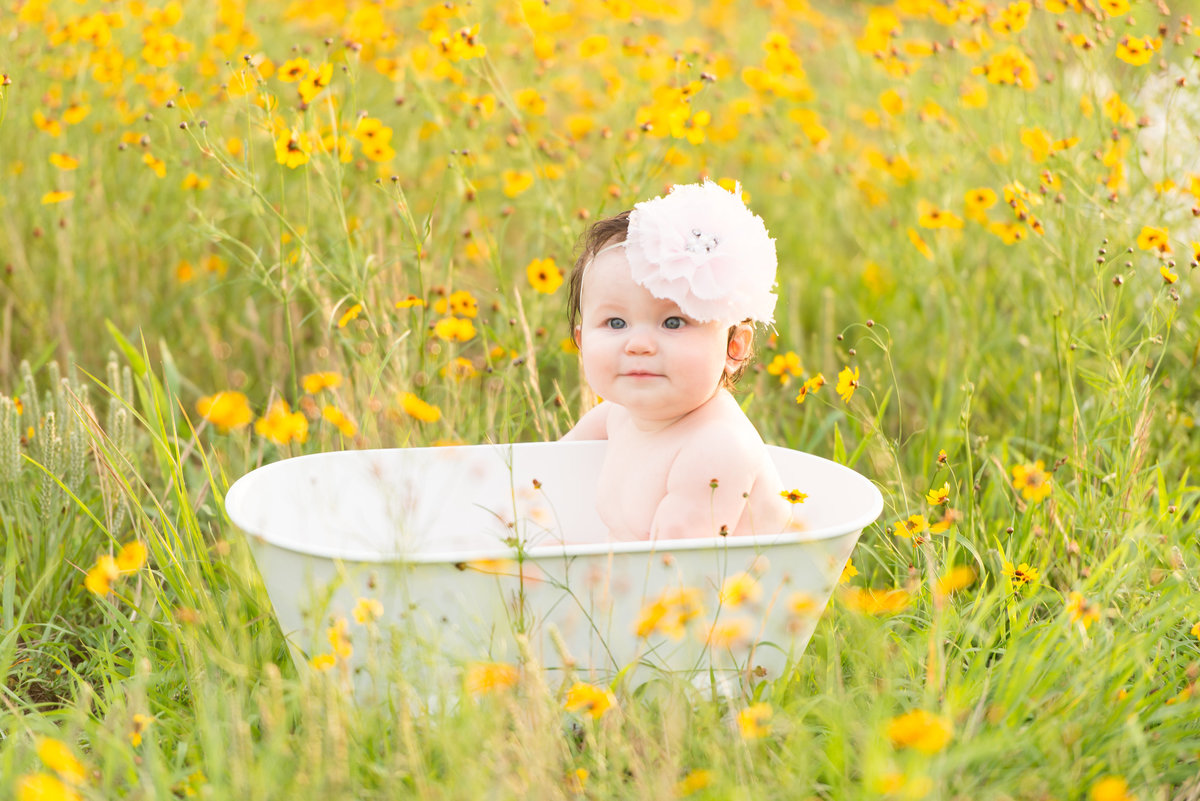 Baby in a tub in a field of wildflowers