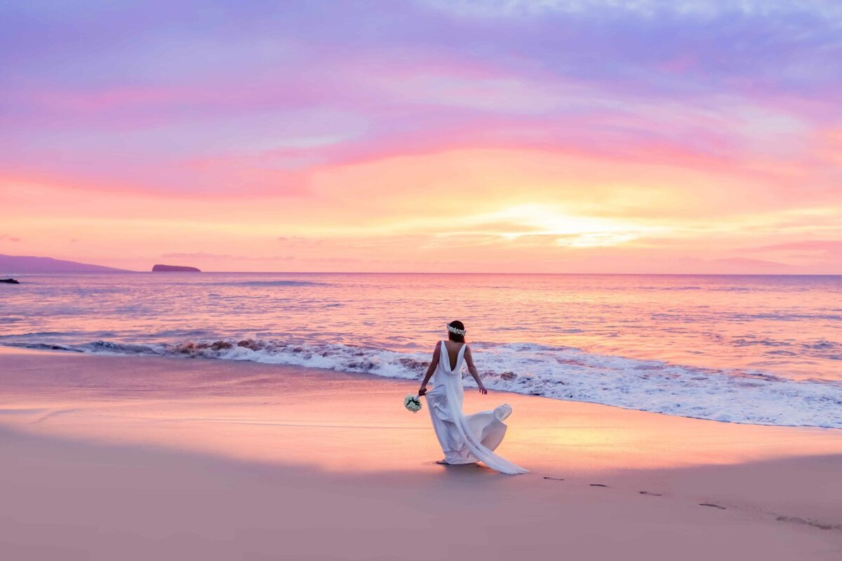 Maui bride holding her dress and walking into the sunset on the beach