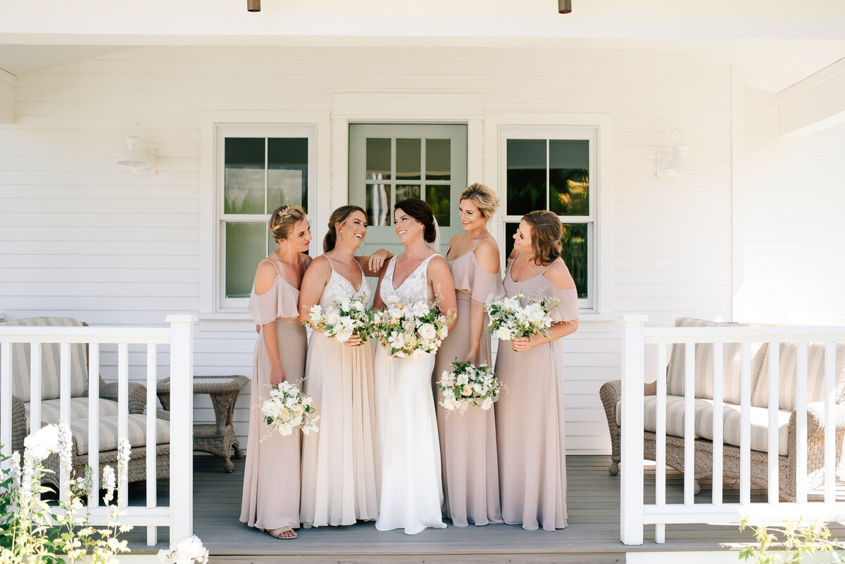 Bridal party in mauve dresses on the porch at Harmony Meadows bridal suite