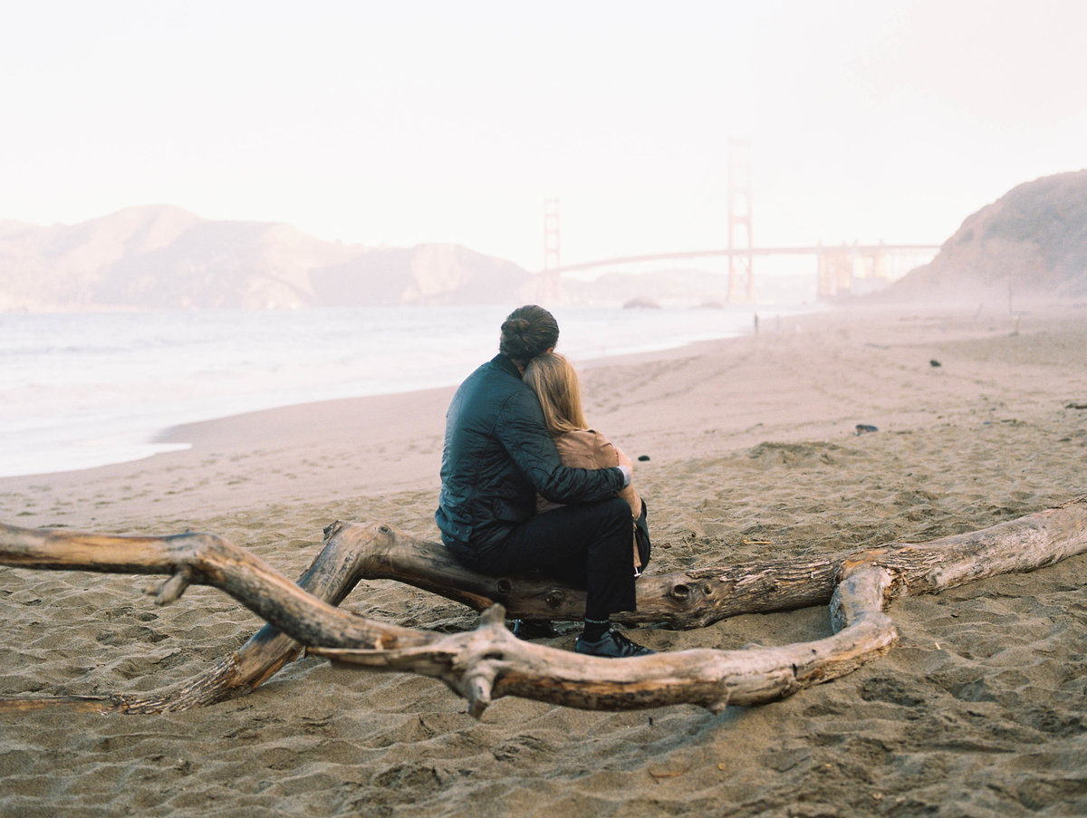 Bakers Beach San Francisco session- couple sitting overlooking golden gate bridge