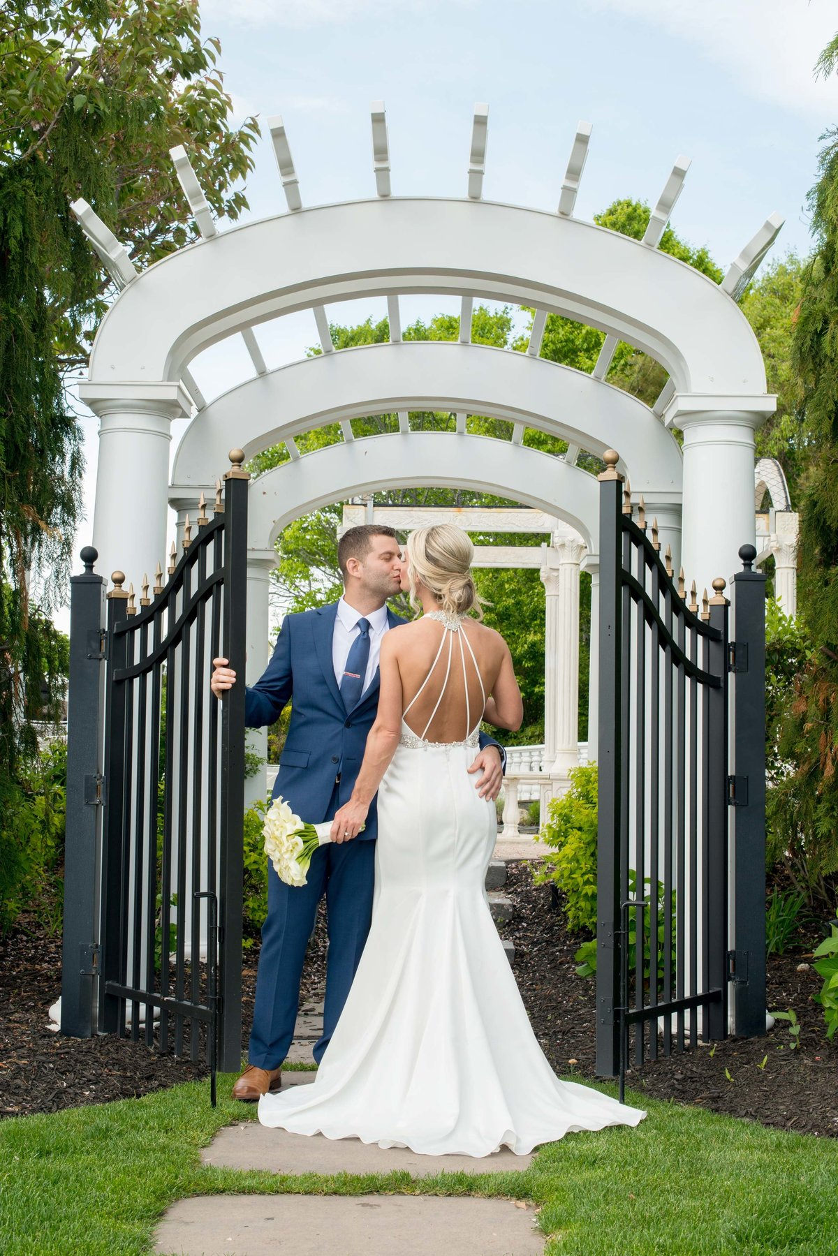 Bride and groom kissing at the gate of Giorgio's Baiting Hollow