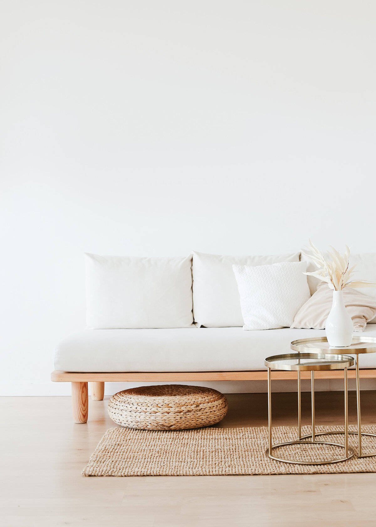 A white sofa is against a white wall, next to a natural sisal rug and jute pouffe with gold coffee tables.