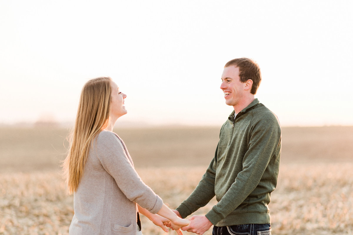 Couple holds hands at sunset engagement session in iowa