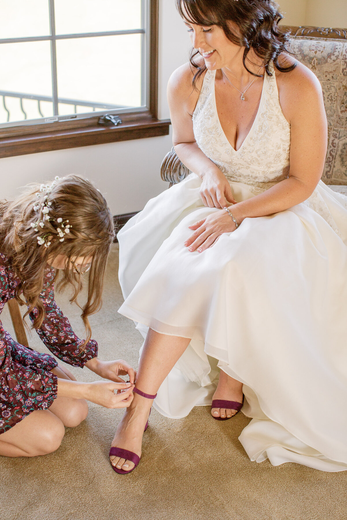 daughter helping mom with wedding sandals