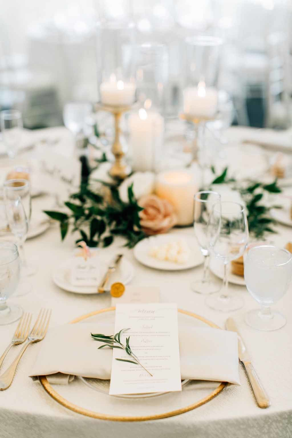 Luxury tent wedding table setting in gold and white with napkin green detail.