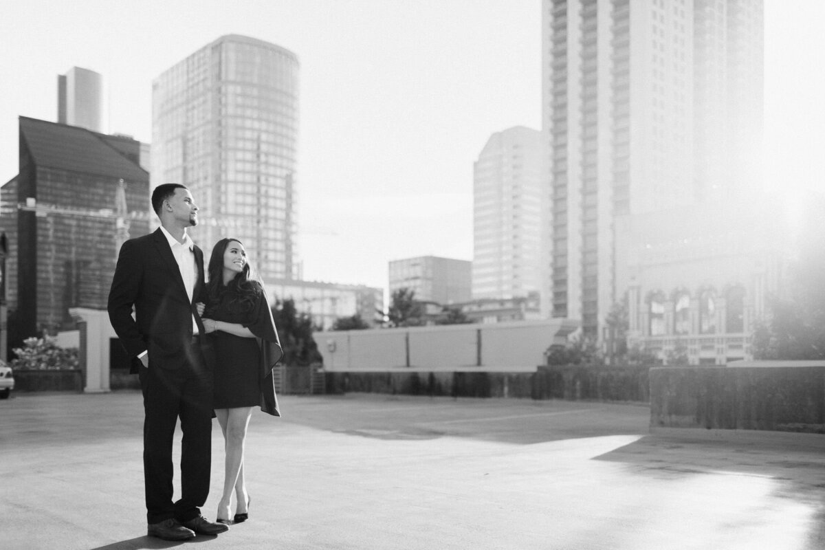 couple standing on rooftop surrounded by tall buildings black and white