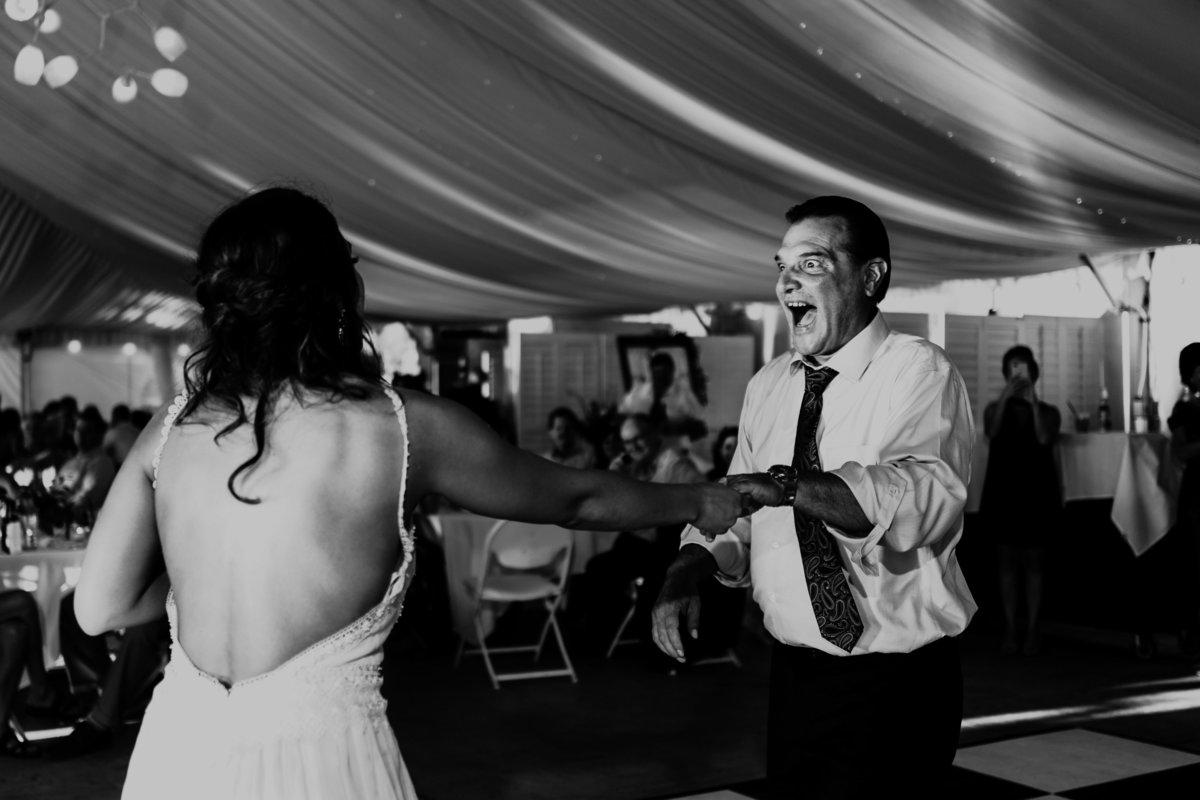 A father and Daughter dance the night away during the reception  as family and friends look on.