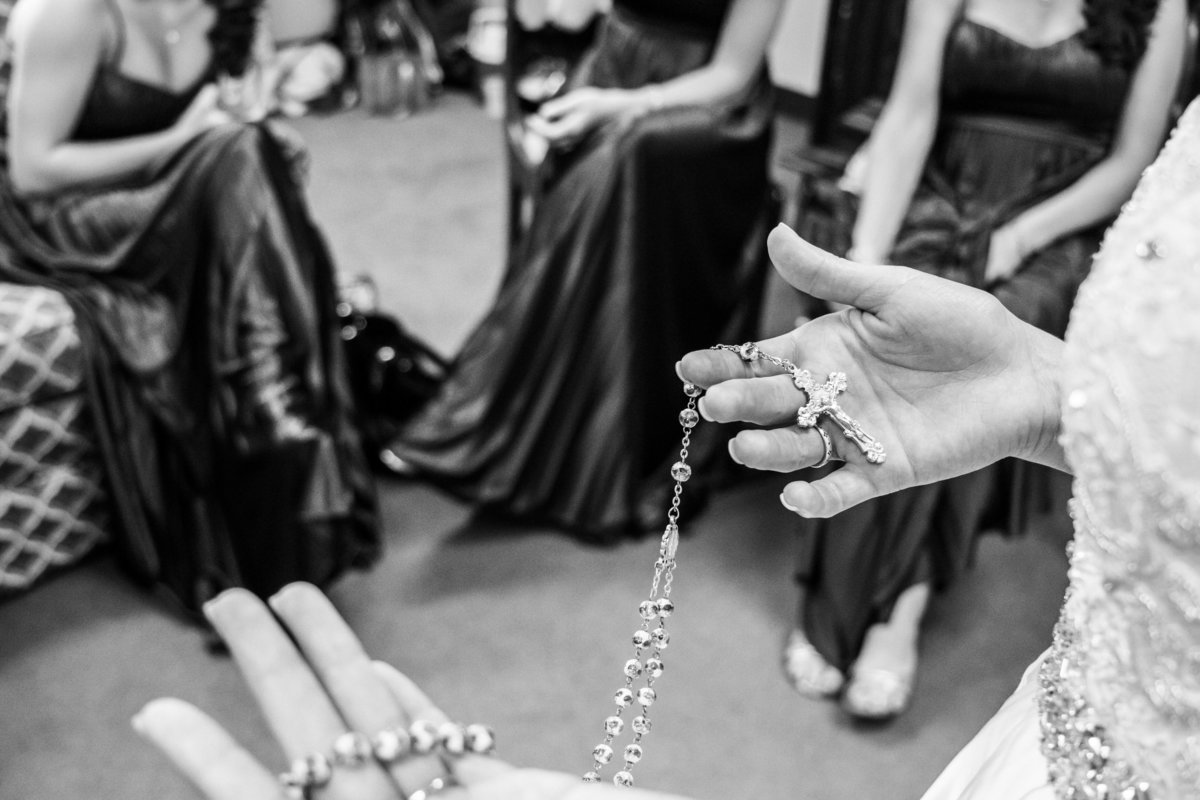 Bride praying the rosary while getting ready for wedding ceremony