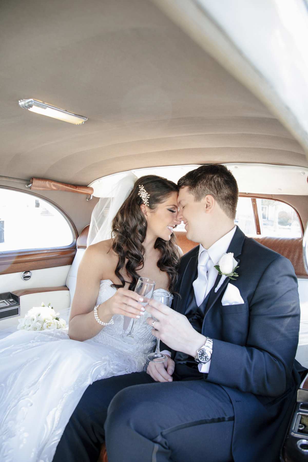 bride and groom in rolls royce after church ceremony