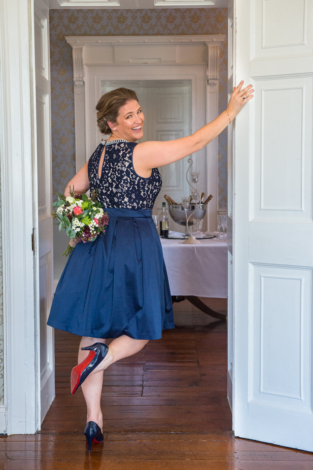 Bride in navy wedding dress wearing navy, red soled shoes