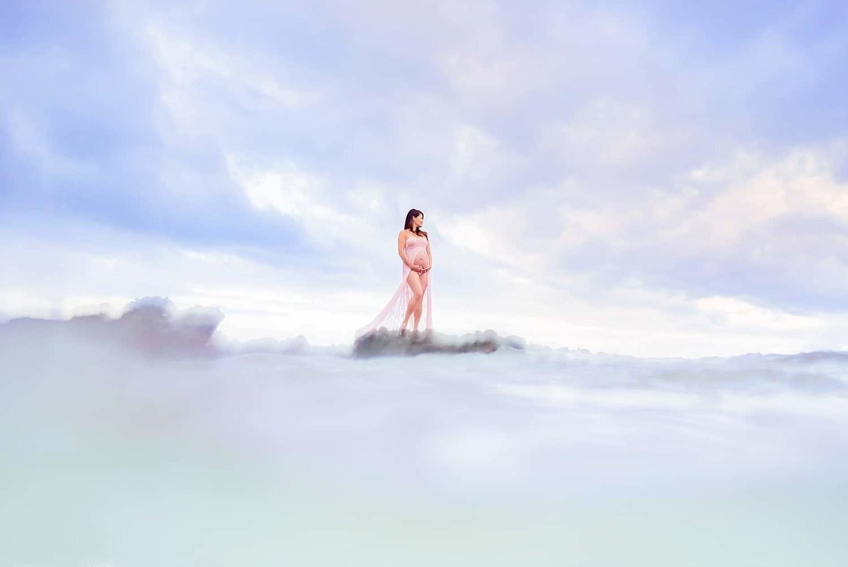 Pregnant woman stands on lava rock and holds her belly as she looks out to sea