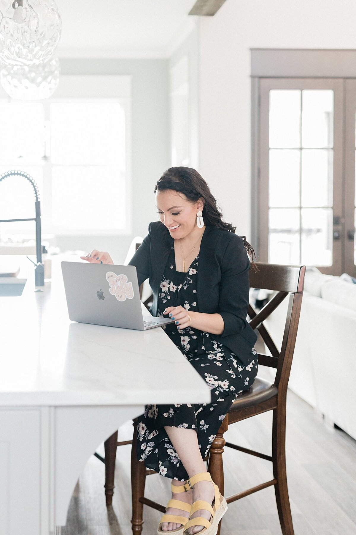 Dolly of. Dolly DeLong Photography is sitting on a tall kitchen. bar stool and typing on her macbook pro