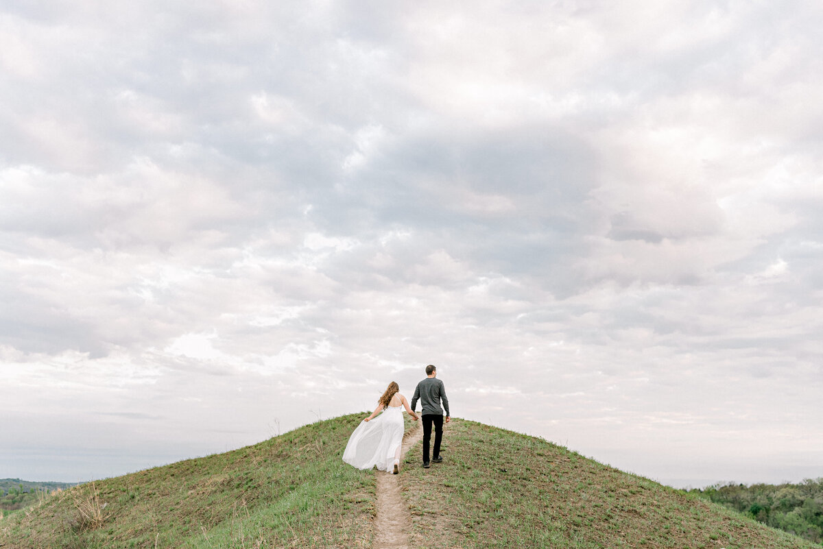 engaged couple walk up a loess hill