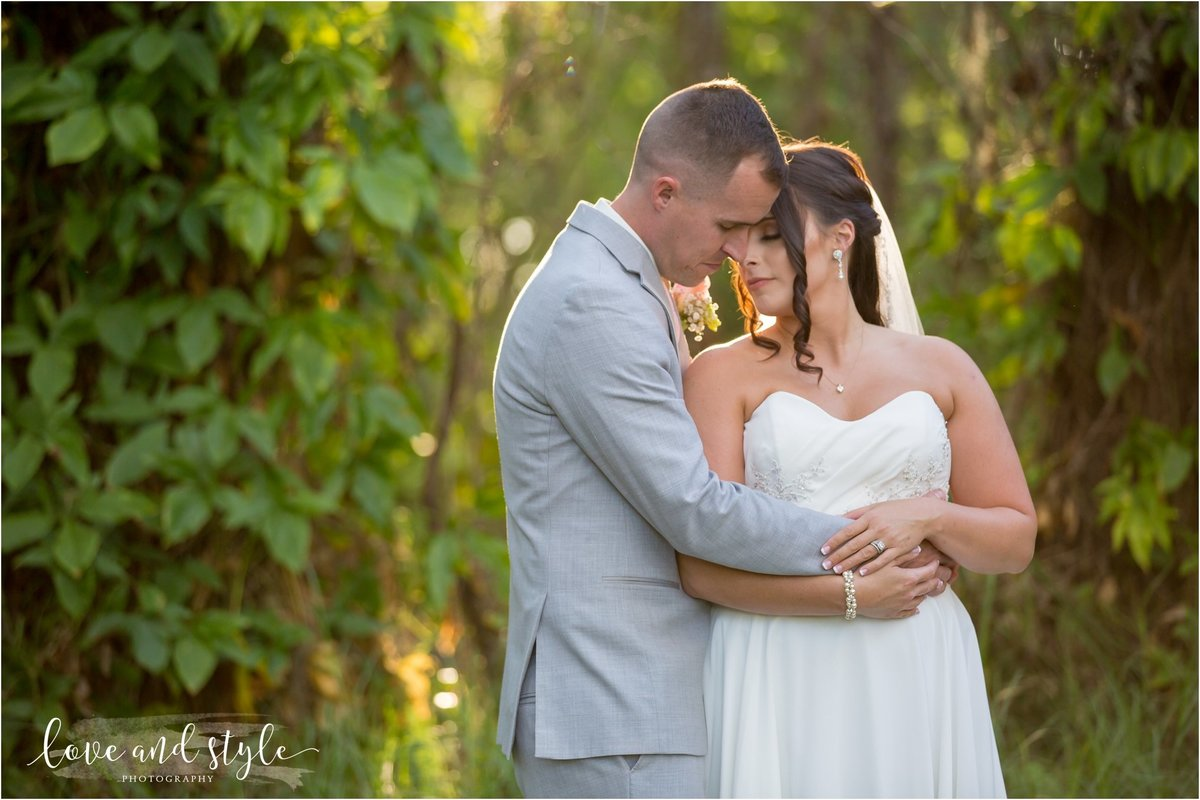Bakers Ranch Wedding Photography with bride and groom embracing  by the trees