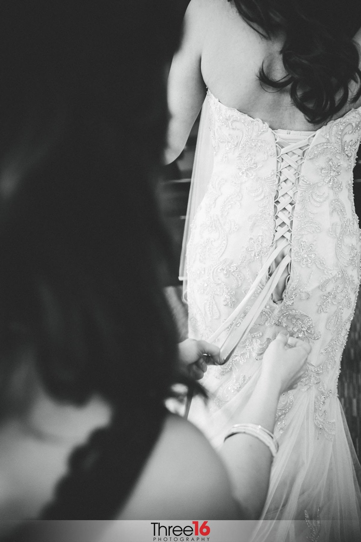 Bride having her wedding gown buttoned up