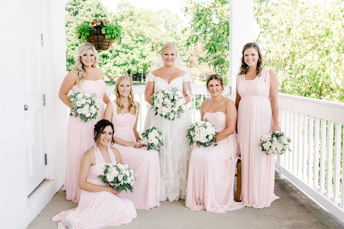 A bride with her bridesmaids in long blush dresses smile at the camera in a formal photo with some sitting, some standing