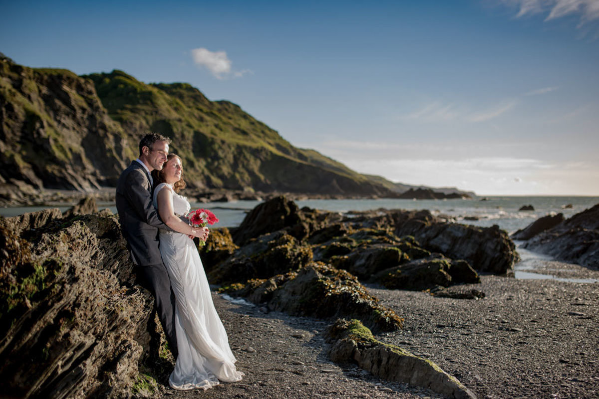 Bride and Groom on the rocks at Tunnels Beaches Devon