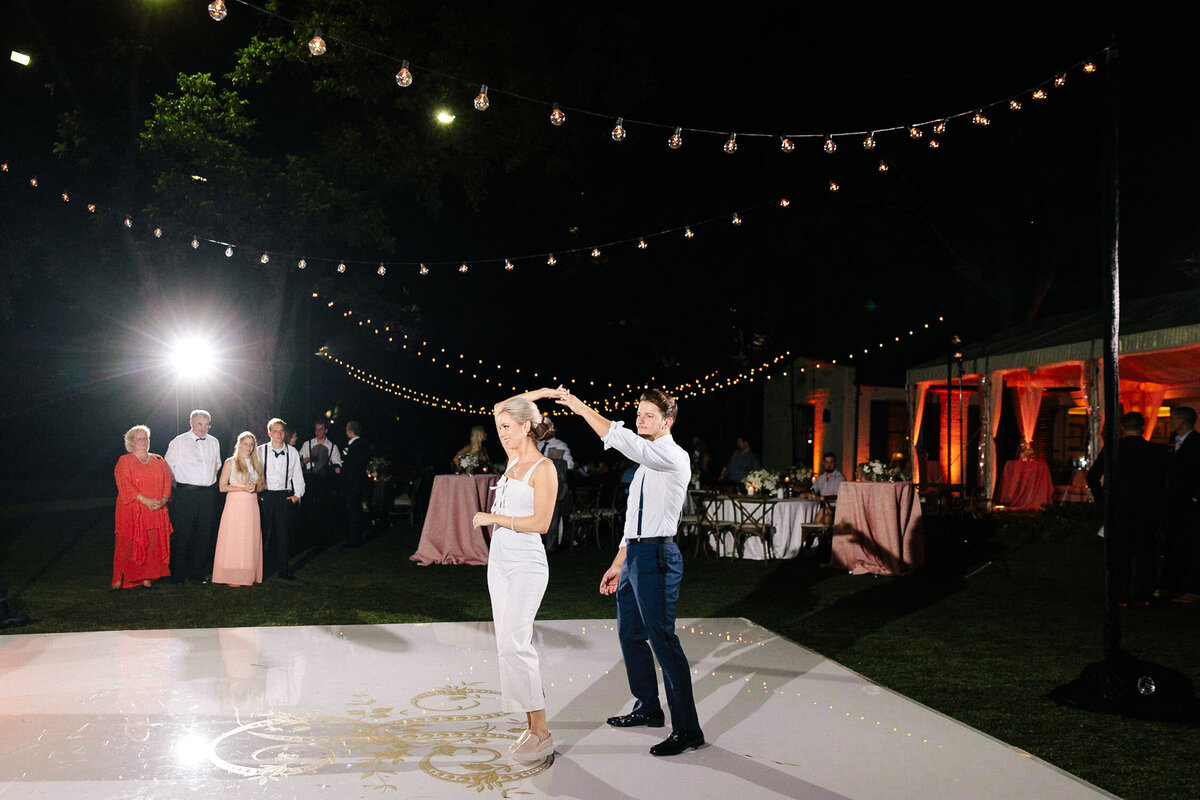 Bride and groom laughing and dancing at wedding reception outdoors dallas arboretum wedding white dance floor