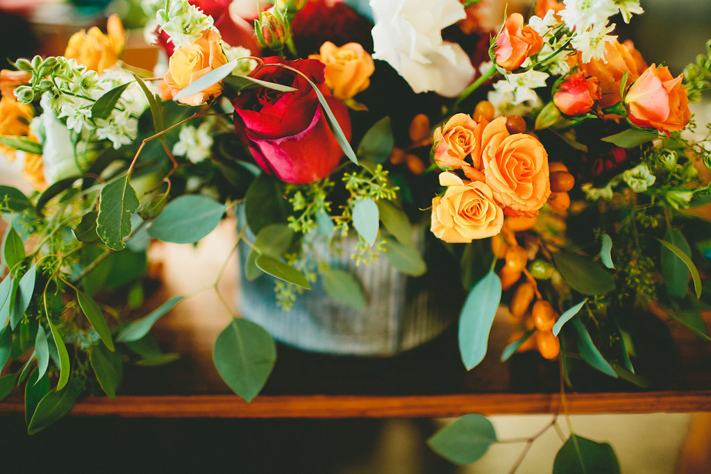 Dinner party flower arrangements with orange and red flowers