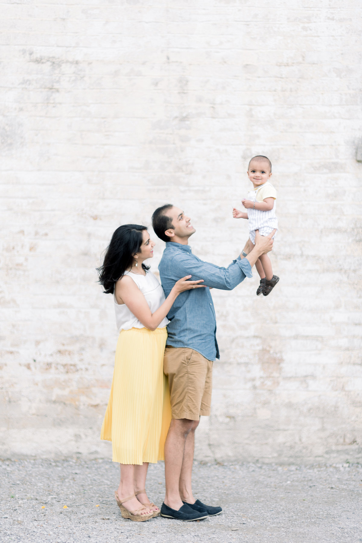 Indian Family of three are smiling at their son and posed in front of a gorgeous white brick wall at Harlinsdale Farm in Franklin, TN
