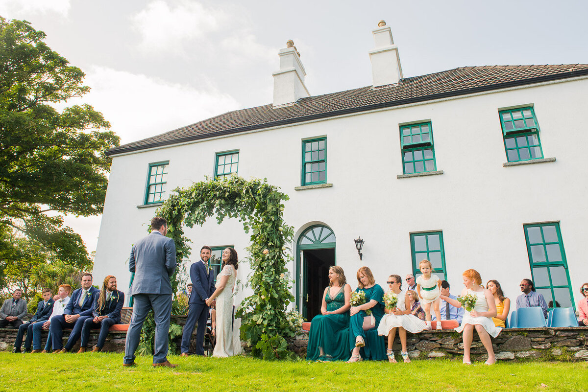 wedding ceremony with floral arch in the garden of Westcove House, Kerry