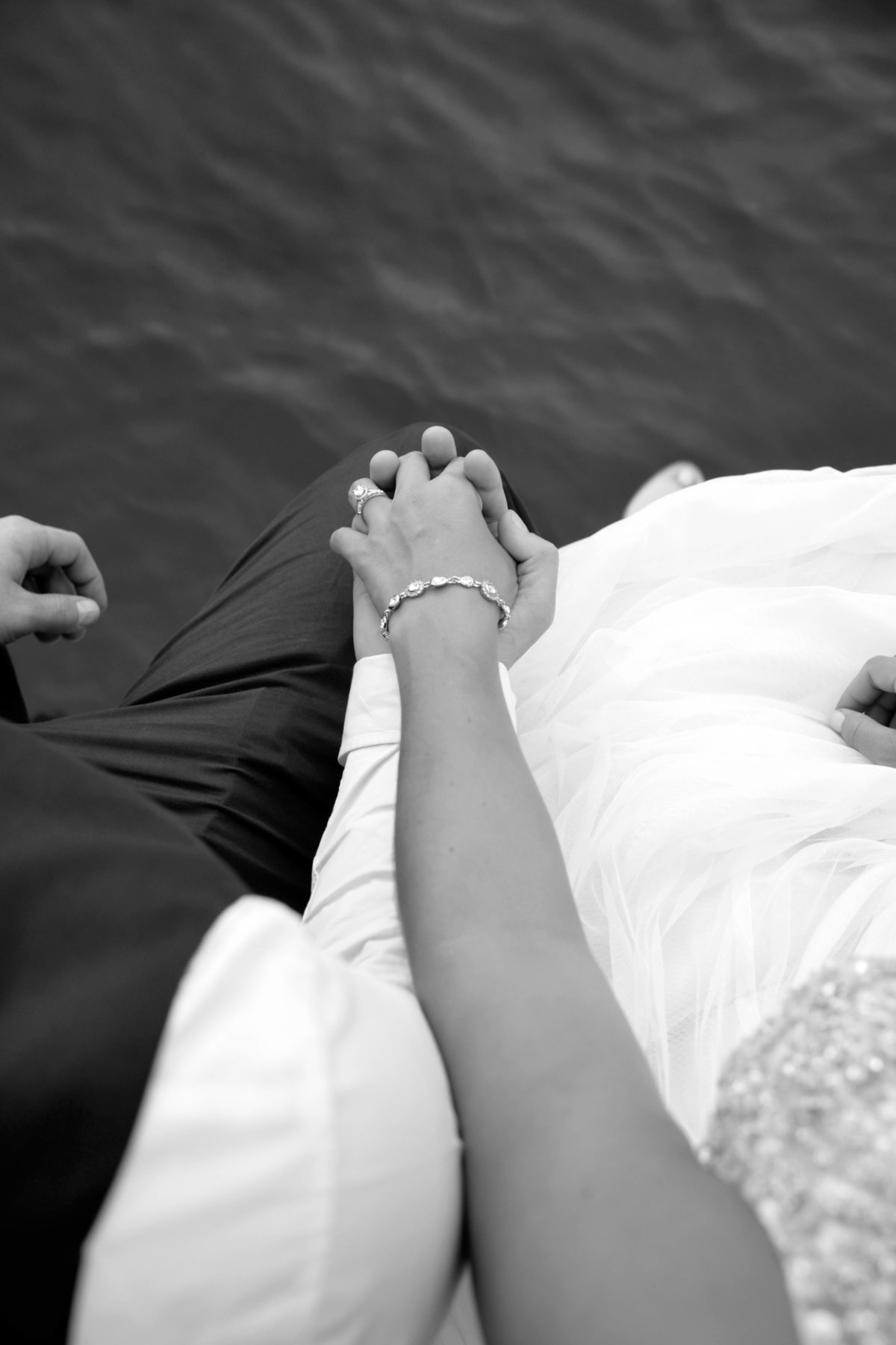 Bride and groom holding hands at the end of the dock at Destin Bay House