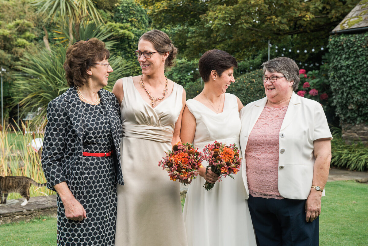 Two brides laughing with their mums in the garden