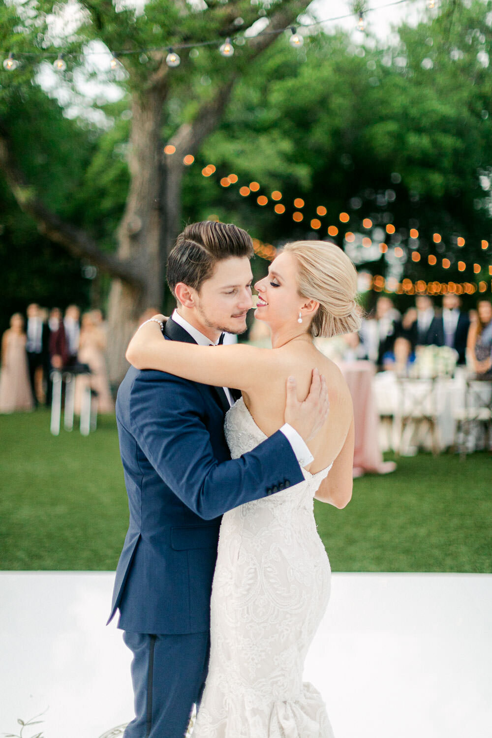 Bride and groom dancing cheek to cheek on white outdoor Arboretum wedding reception