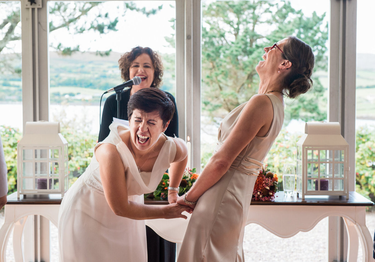 Two brides at their wedding ceremony, laughing out loud