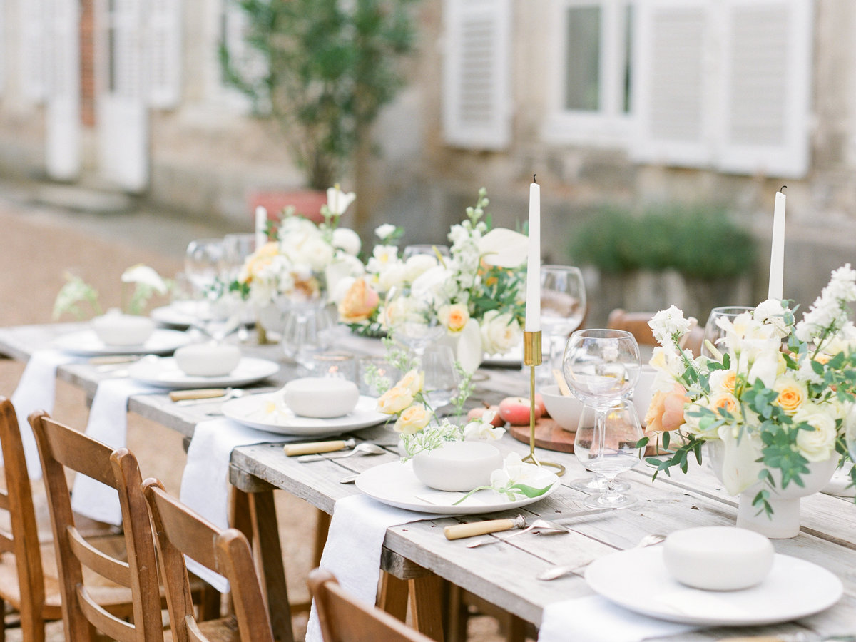 Outdoor wedding table set with white plates and green and yellow florals
