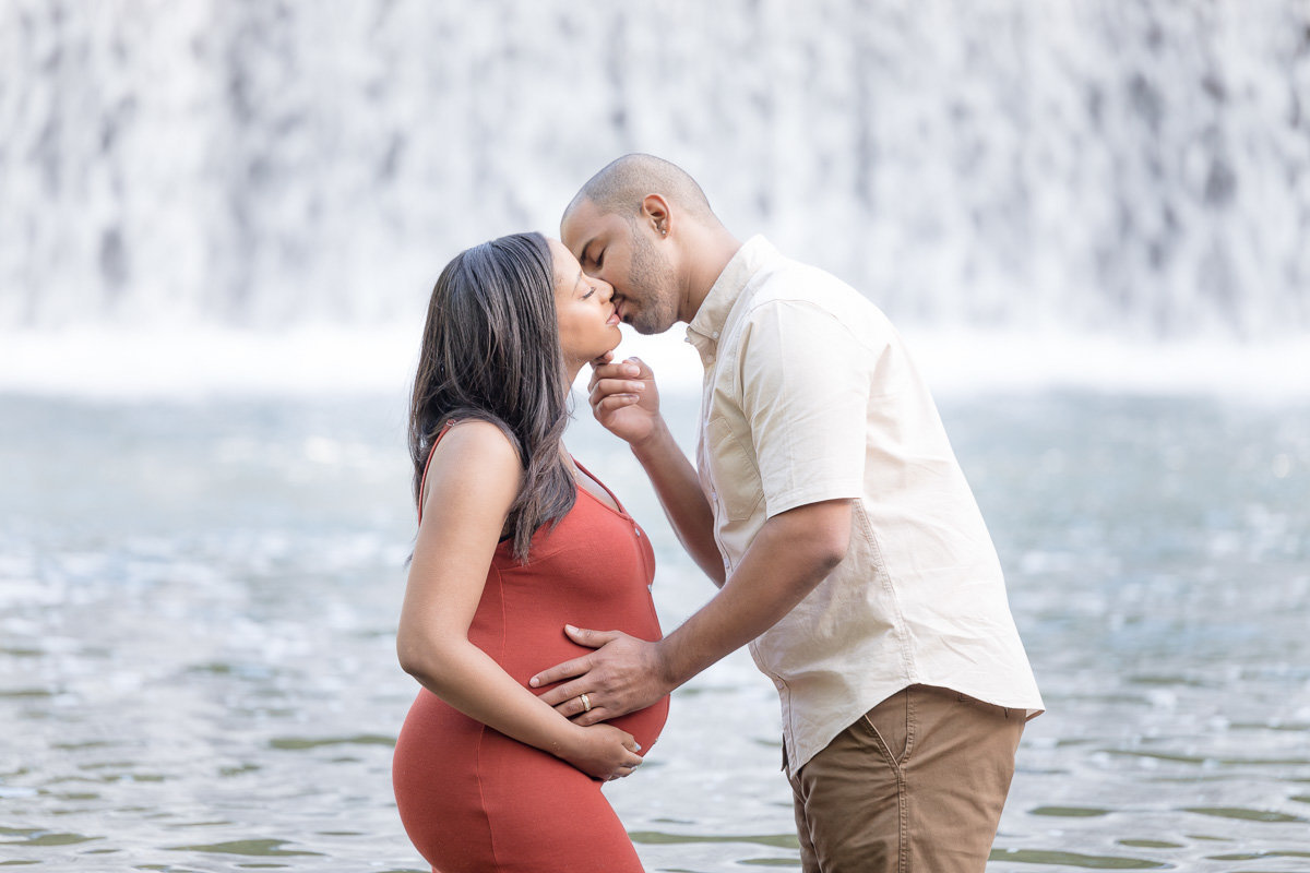 husband and pregnant wife kiss in front of Ellicott City waterfall
