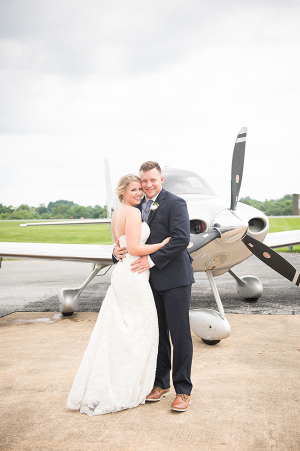 A bride and groom pose in front of an airplane