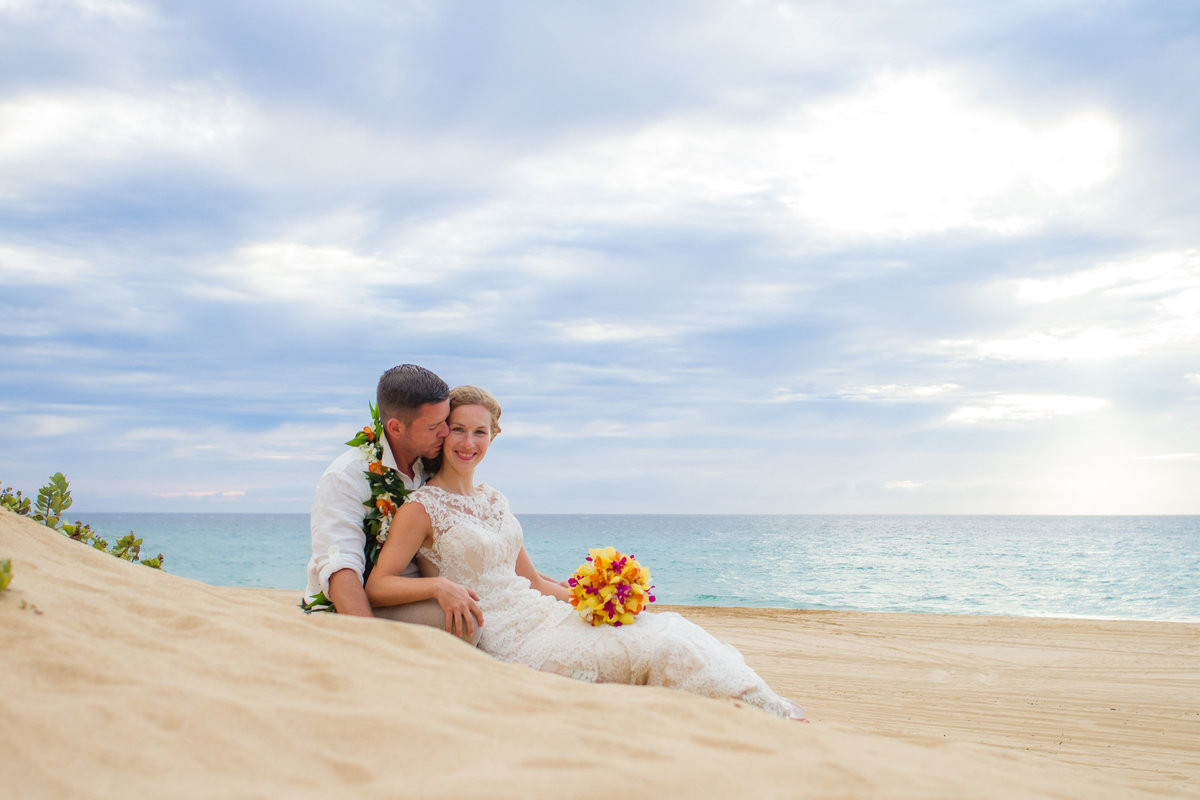 Wedding couple sitting in the sand at Kauai beach.