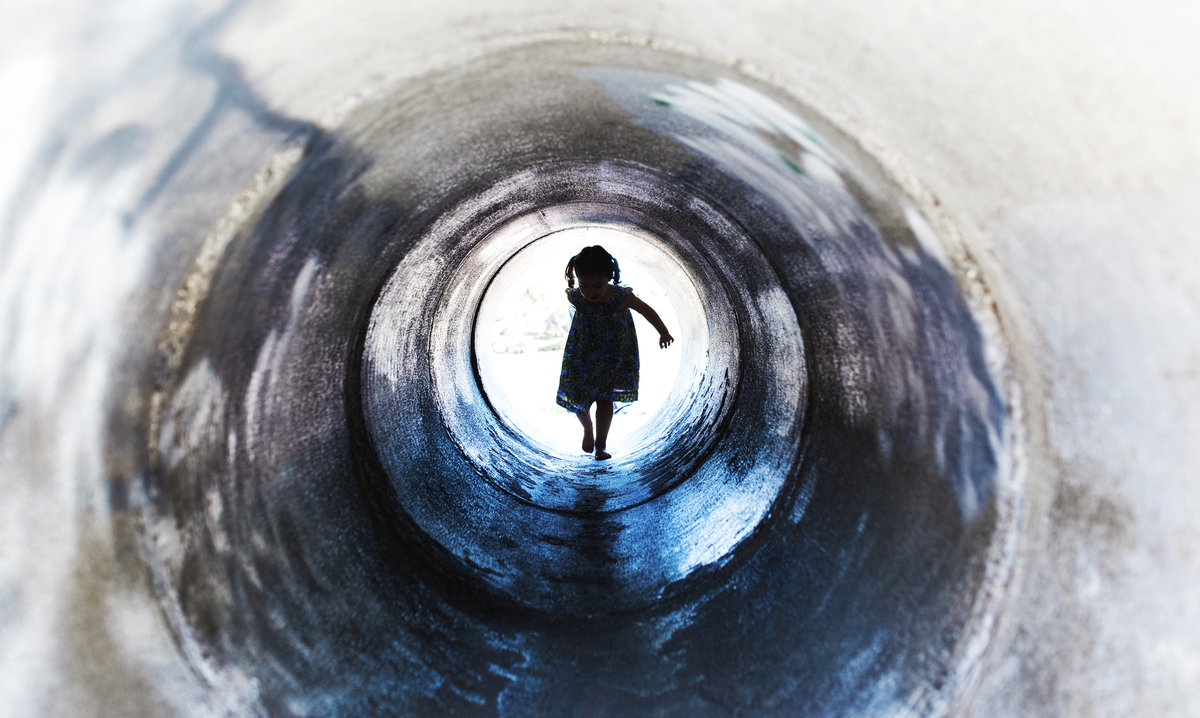 charlotte documentary photographer jamie lucido captures a beautiful and artistic silhouette of a child coming through a tunnel at a playground, Dennis the Menace in Monterey, California