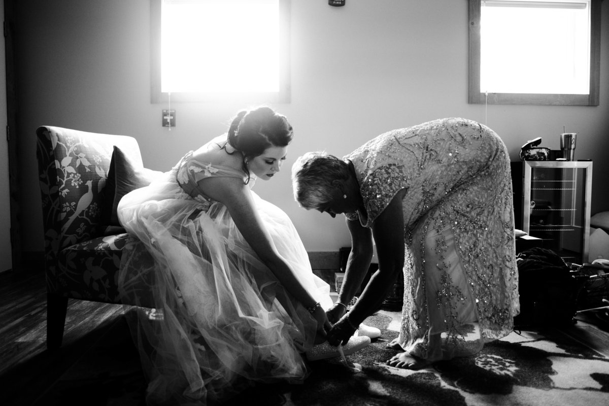 One of the top wedding photos of 2019. Taken by Adore Wedding Photography- Toledo Ohio Wedding Photographers. This photo is of mother helping her daughter put on her shoes before the wedding ceremony