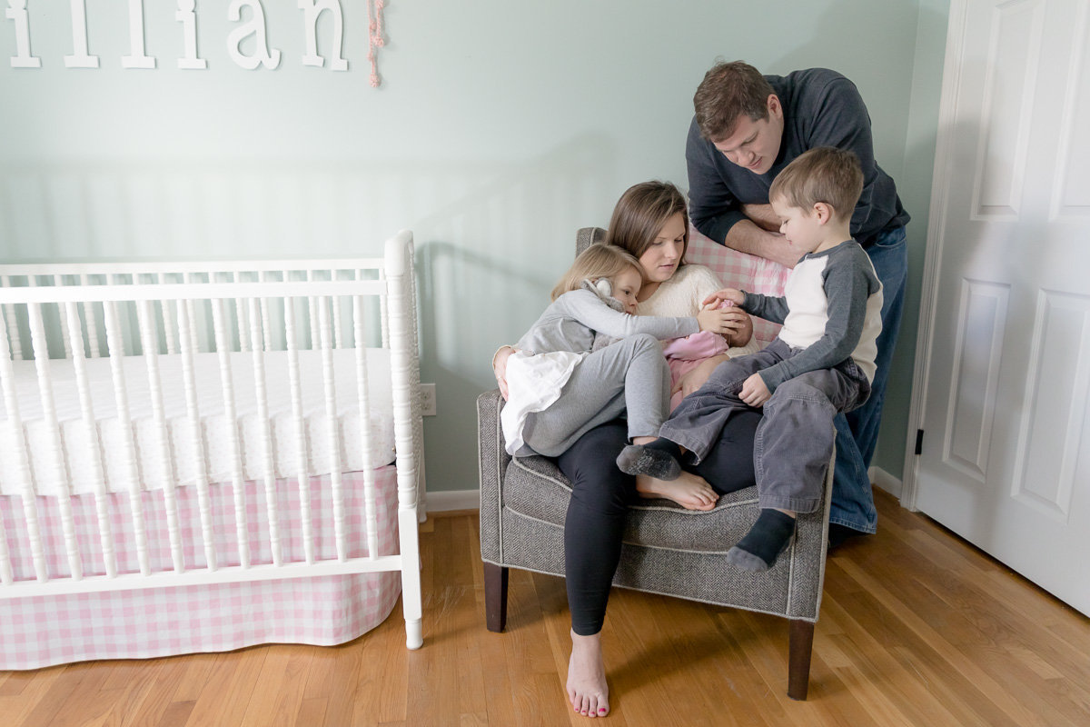 The whole family piles in close to love on newborn baby girl
