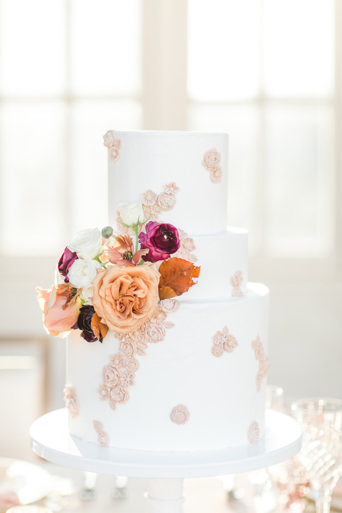 Wedding cake with lace motifs and pink and orange flowers