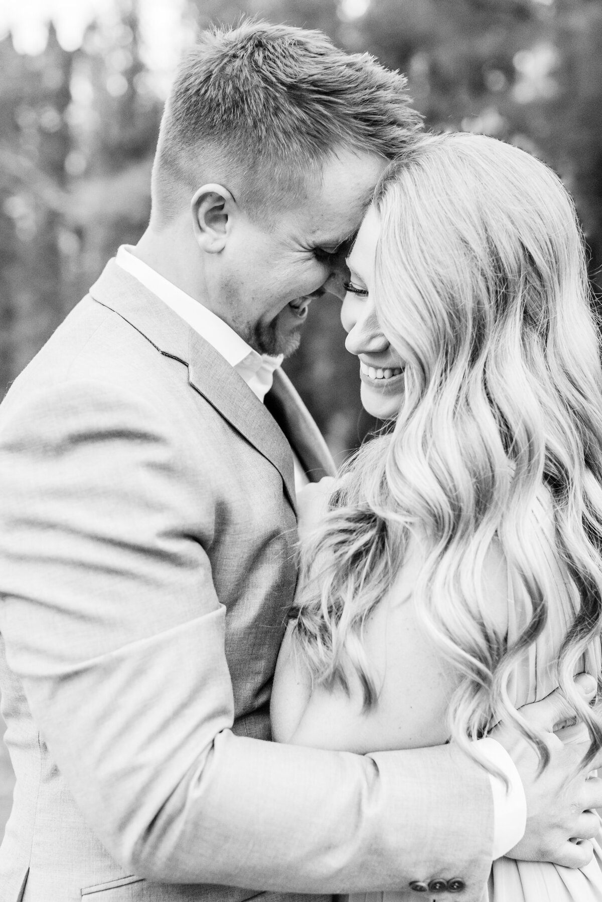 Couple-share-a-special-moment-laughing-as-his-forehead-is-on-her-temple-during-their-fall-engagement-session-at-Cranberry-Creek-Gardens