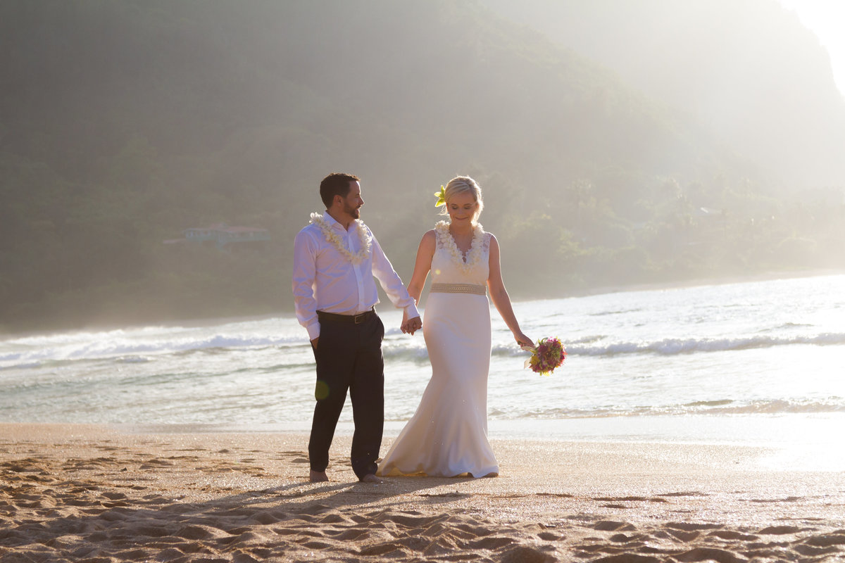 Wedding couple walking along the beach in Kauai.