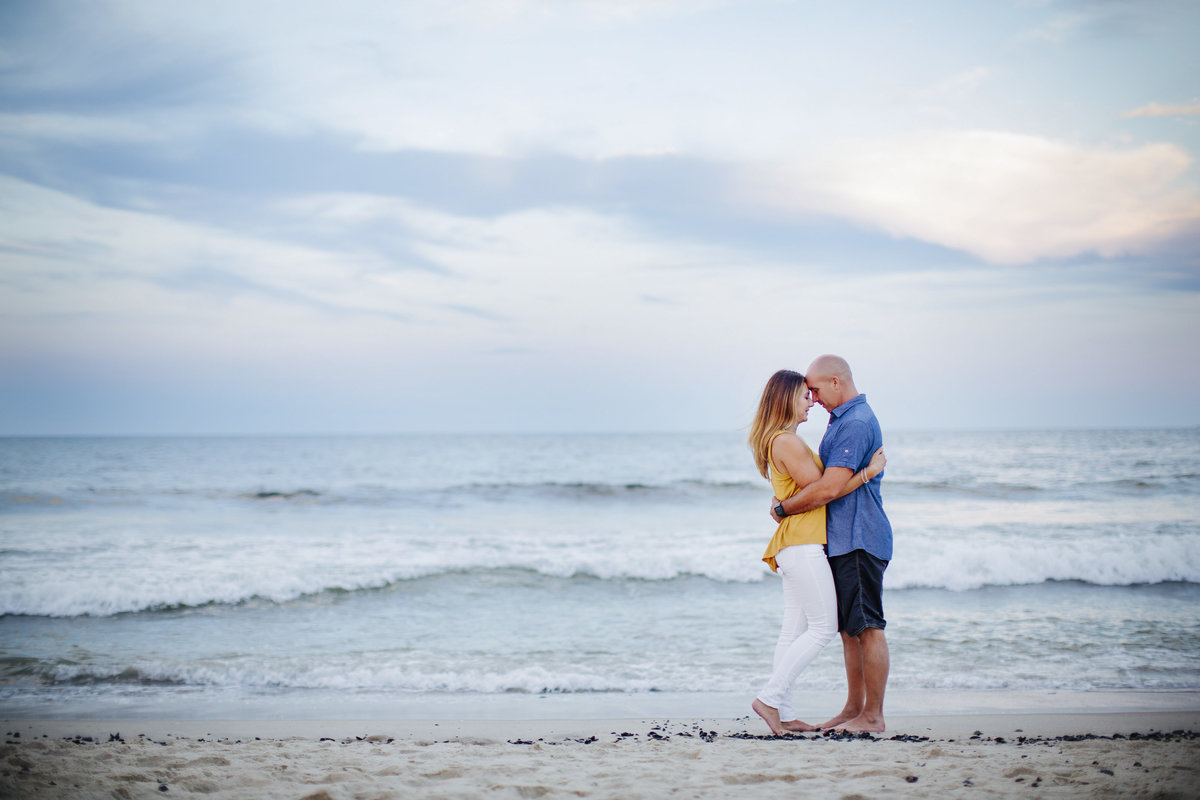 engaged couple hugging on beach at spring lake