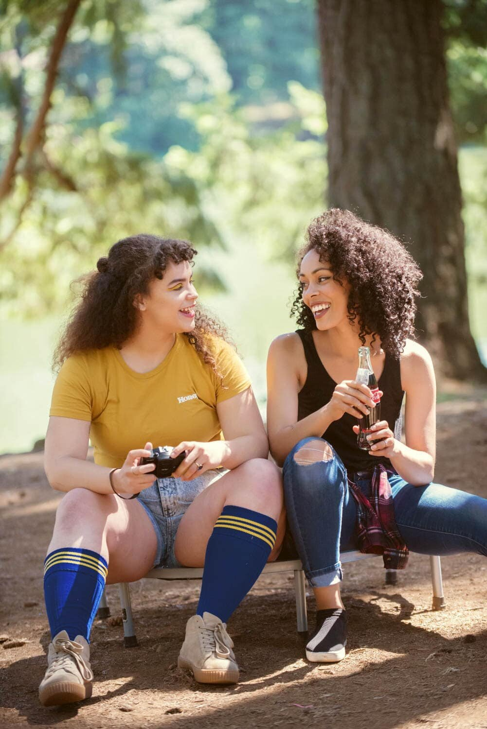 two girls dressed for 80s summer camp sit and talk