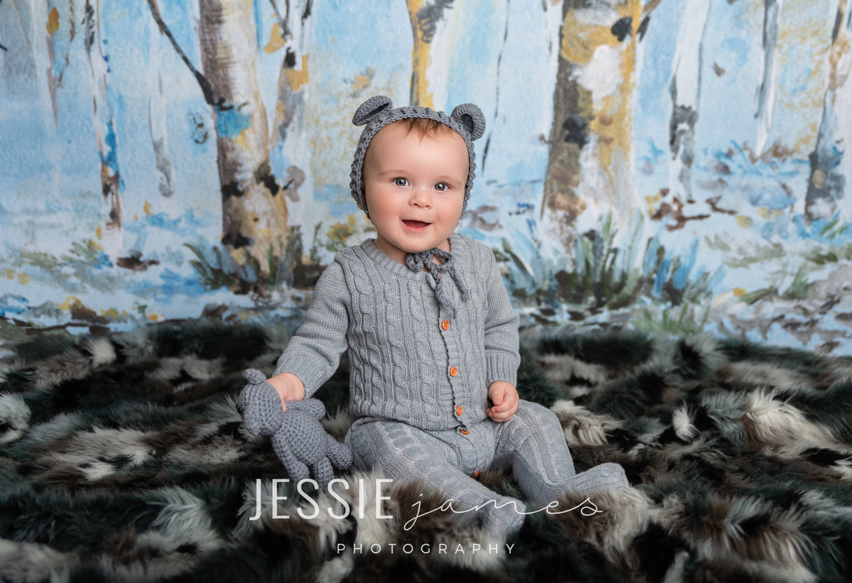 baby boy wearing a bear costume for a milrstone photography session