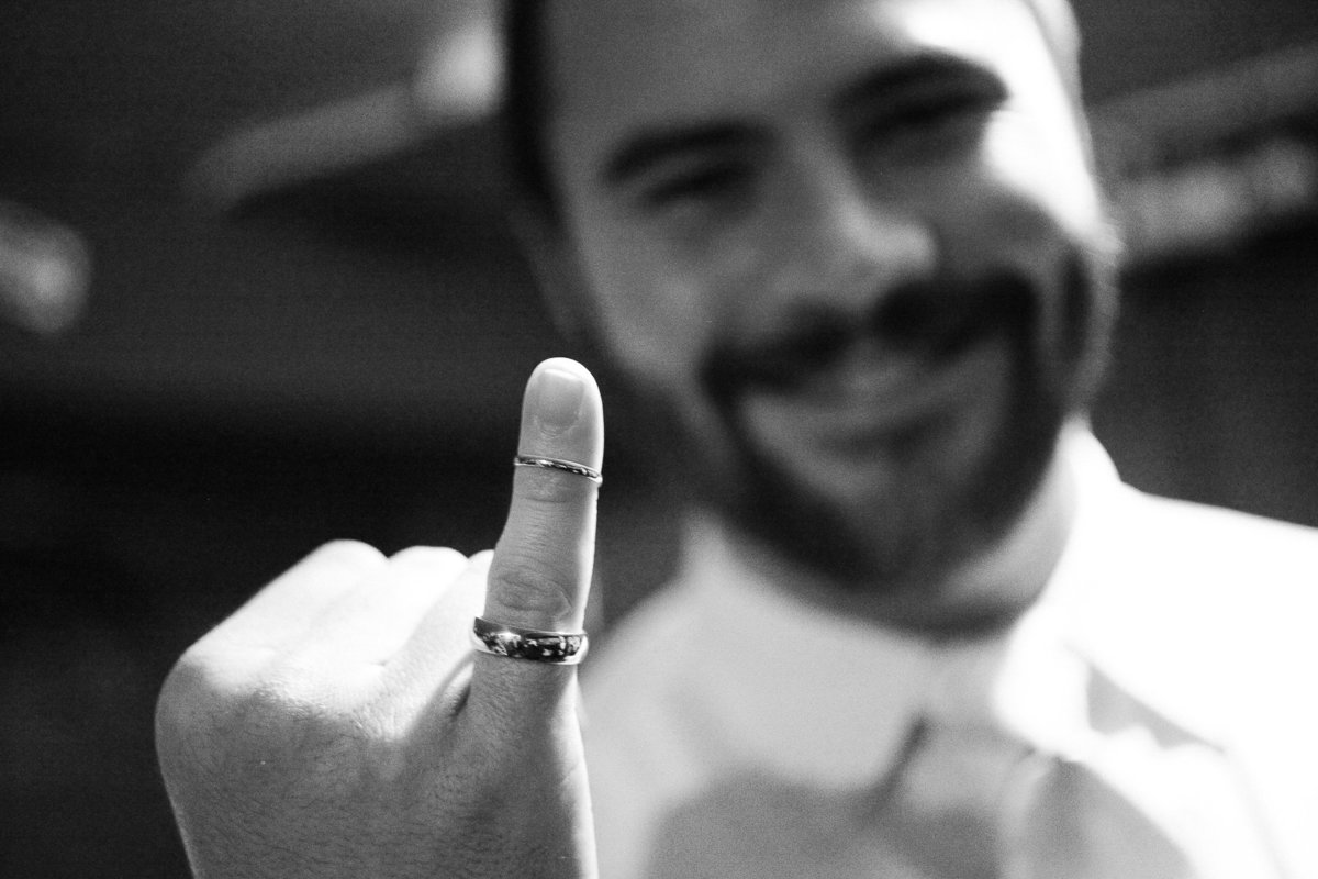 A groom shows off the wedding rings.
