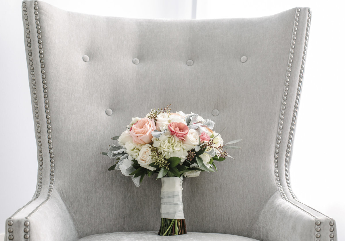 brides boutique resting on grey chair before wedding