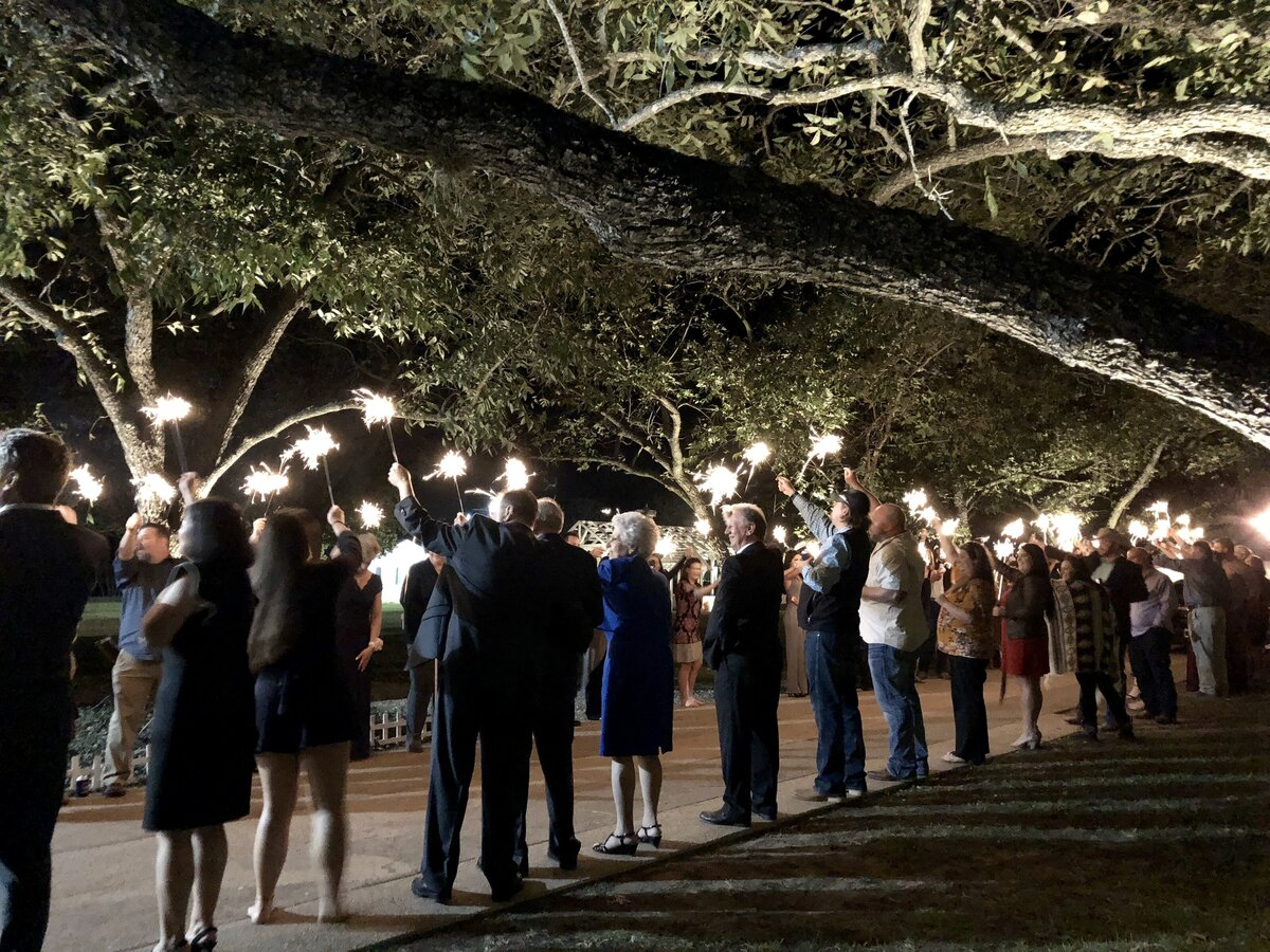 The grand exit for a wedding at the Grand Texana. Guests are holding sparklers underneath the pecan trees