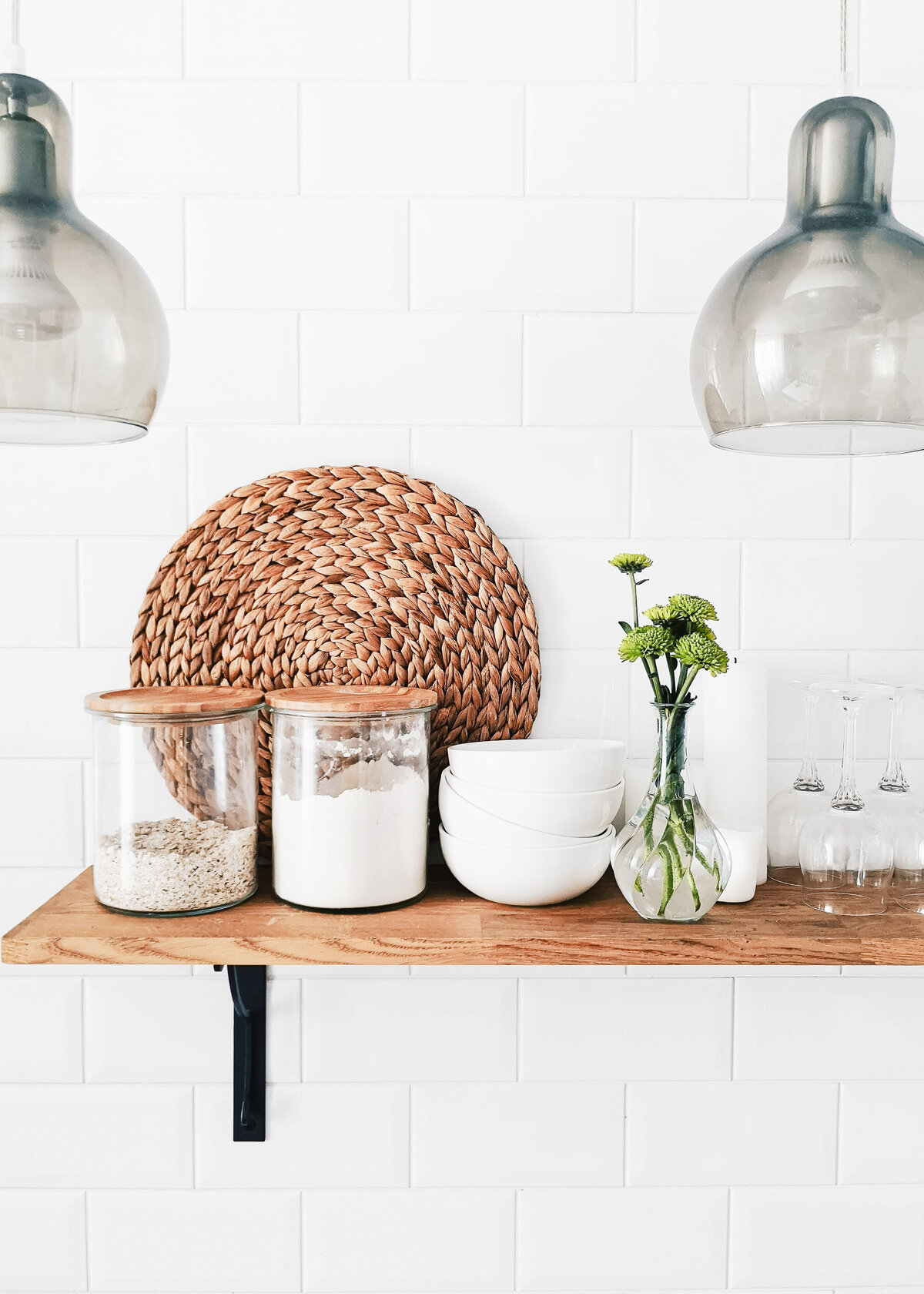 A wooden shelf holds a rattan placemat against a white tiled wall with smoky glass pendants.